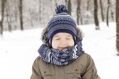 Child in winter, portrait squint blink. Photo of a child while walking in a winter park, close-up portrait. the boy is dressed in warm clothes and squinted Royalty Free Stock Photography