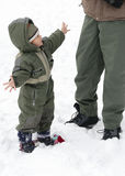 Child in winter snow with parent Stock Image