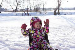 Child on winter and snowy background. Making snow angel while lying on snow.  Stock Image