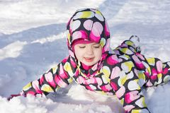 Child on winter and snowy background. Making snow angel while lying on snow.  Royalty Free Stock Photos