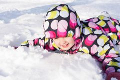 Child on winter and snowy background. Making snow angel while lying on snow.  Royalty Free Stock Image