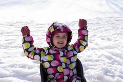 Child on winter and snowy background. Making snow angel while lying on snow.  Stock Photos
