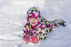 Child on winter and snowy background. Making snow angel while lying on snow.  Stock Photography