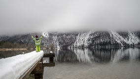 Child in winter suit standing on a snowy pier on a beautiful mis Royalty Free Stock Photos