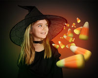Child Witch Waiting for Halloween Candy Corn on Black. A little girl is wearing a witch halloween costume with a black hat. The child is imagining candy corn for Royalty Free Stock Photos