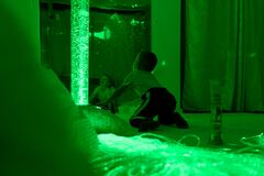 Free Child With Intellectual Disability In Sensory Stimulating Room, Snoezelen. Autistic Child Interacting During Therapy Session. Stock Photos - 200794383