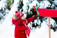 Free Child With Letter To Santa At Christmas Mail Box In Snow Royalty Free Stock Images - 103948279