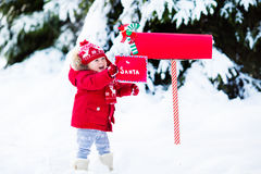 Free Child With Letter To Santa At Christmas Mail Box In Snow Stock Photos - 80775423