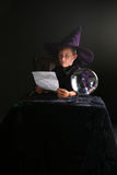 Child in wizard costume consulting his spell Stock Photo