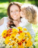 Child and woman with bouquet of flowers Stock Images