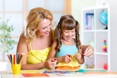 Child with woman cutting out scissors paper in Royalty Free Stock Photos