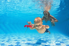 Child with woman diving for a red flower in pool Stock Photos