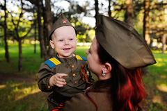 Child and woman dressed in military uniform against nature background royalty free stock photo