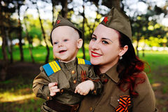 Child and woman dressed in military uniform against nature background Stock Images