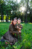 Child and woman dressed in military uniform against nature background Stock Photography