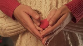 Child and woman hands holding toy heart, concept of parental love and care