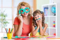 Child with woman have a fun cutting out scissors Royalty Free Stock Photos