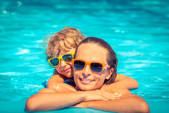 Child and woman playing in swimming pool Royalty Free Stock Photos