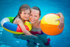 Child and woman playing in swimming pool Stock Photo