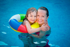 Child and woman playing in swimming pool Stock Photos