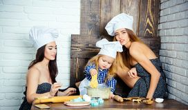 Child and women kneading dough stock photo