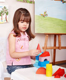 Child with wood block in play room. Stock Photo