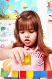 Child with wood block in preschool. Stock Image