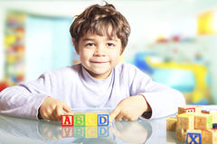 Child  with wooden cubes. Child playing with wooden cubes Royalty Free Stock Images