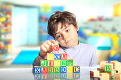 Child with wooden cubes. Child with colorful wooden cubes Royalty Free Stock Images