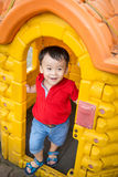 Child at wooden door. Small smiling happy child playing peeping out of a wooden playhouse or a small garden shed door royalty free stock image