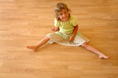Child on wooden floor. Child sits on wooden floor Royalty Free Stock Photo