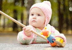 Child with a wooden toy. Baby girl in a knitted hat playing with a wooden toy stock photos