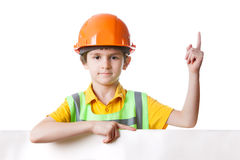 Child in work clothes with billboard holds finger up. Child in work clothes with billboard, isolated on white background. His finger up royalty free stock photography