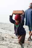 Child workers. SONAKHALI, INDIA - JANUARY 17: child workers carry bricks carrying it on his head in Sonakhali, West Bengal, India on January 17, 2009 stock photo