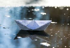 Child workers a paper boat from school notebook] swims in spring. Pools stock photography