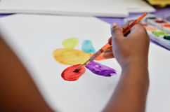 Child working on art project. Kid uses brush to paint with water color Royalty Free Stock Photos