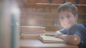 Child working in the classroom surrounded by animation of bokeh effect. Digital composite of Caucasian child reading a book in the classroom surrounded by stock footage