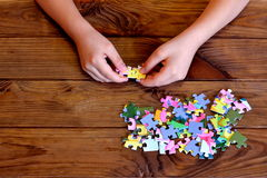 Child working on jigsaw puzzle. Child holding a puzzle in hands. Group of jigsaw puzzles on wooden table Royalty Free Stock Photography