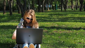 Child working on laptop in nature. A teenage girl wearing sunglasses sits on the grass in the park. Girl sunny outdoor day with la stock video footage