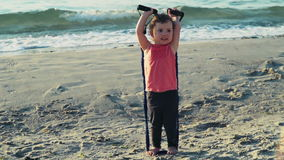Child works out on the beach slow motion stock video