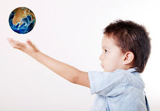 Child and world. Child looking up with hand extended and taking the world stock photography