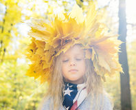 Child with wreath of autumn leaves Stock Photography