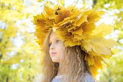 Child with wreath of autumn leaves Stock Photos