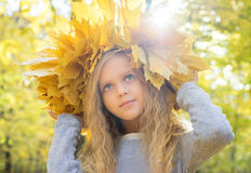 Child with wreath of autumn leaves Stock Image