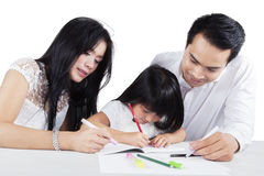 Child write on the book with her parents Royalty Free Stock Photography