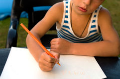The child writes. The little boy studies to write a word mama Stock Photo