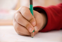 Child writes. Girl wrote a children's hand with a pencil sheet of white paper with a picture sleeve on red soft background on a table studying a happy Royalty Free Stock Photography