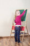 Child writes on the blackboard. A small child will practice writing on the blackboard and looking at the camera Royalty Free Stock Images