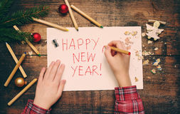 Child writes `Happy New Year` on a white sheet of paper. Child`s hands, the sheet of paper, pencils and Christmas decorations Royalty Free Stock Images