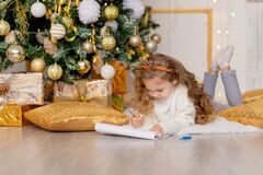 A child writes a letter for Santa Claus under a gold-decorated Christmas tree